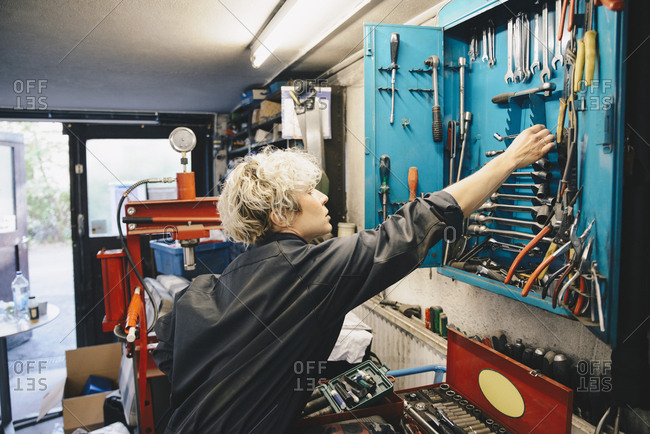 Female mechanic removing work tool from cabinet at auto repair shop