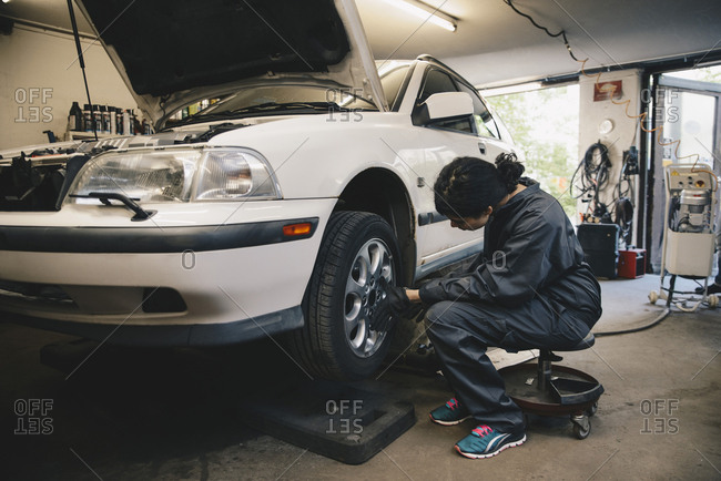 Side view of female mechanic examining car wheel at auto repair shop