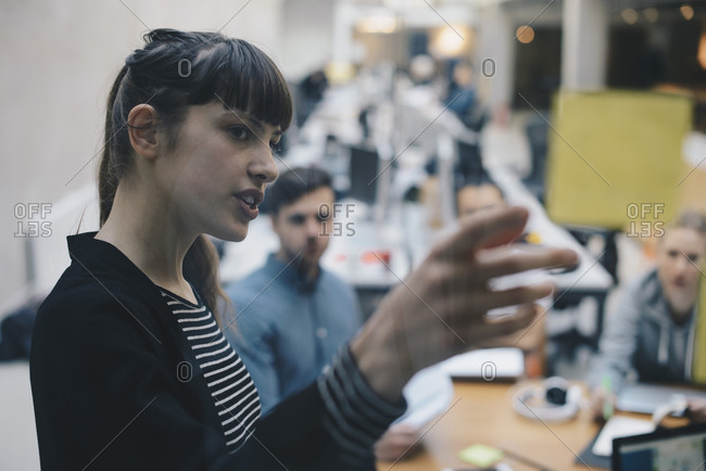 Computer programmer explaining adhesive note to colleagues in office