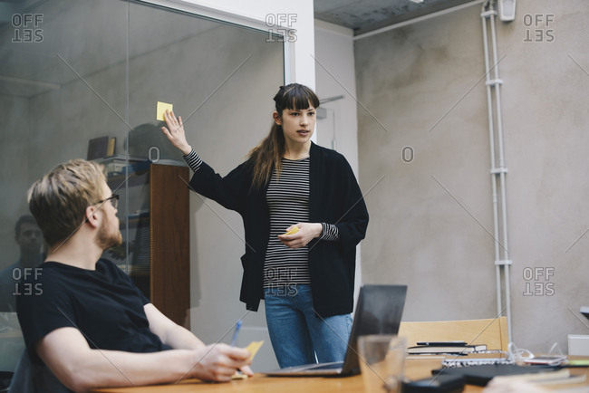 Female computer programmer showing adhesive note while giving presentation to colleague in office
