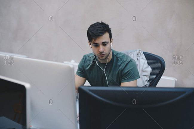 Male computer programmer using desktop PC in office