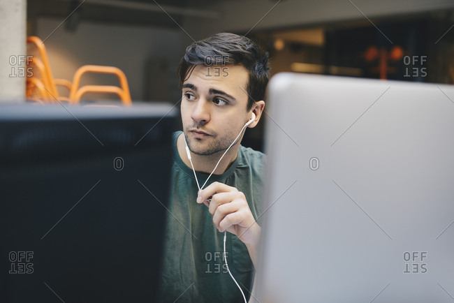 Thoughtful computer programmer wearing in-ear headphones in office