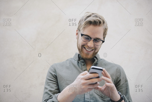 Happy male computer programmer using smart phone against beige wall in office