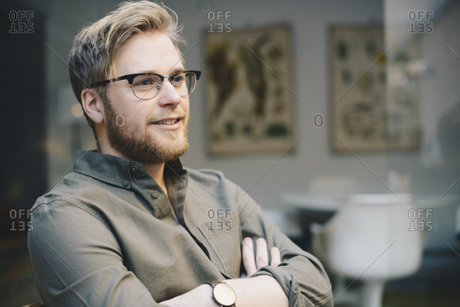 Thoughtful male computer programmer standing arms crossed in office
