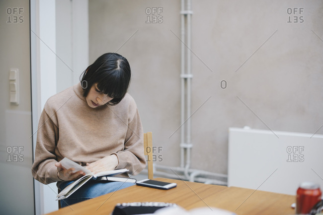 Female computer programmer reading diary in office