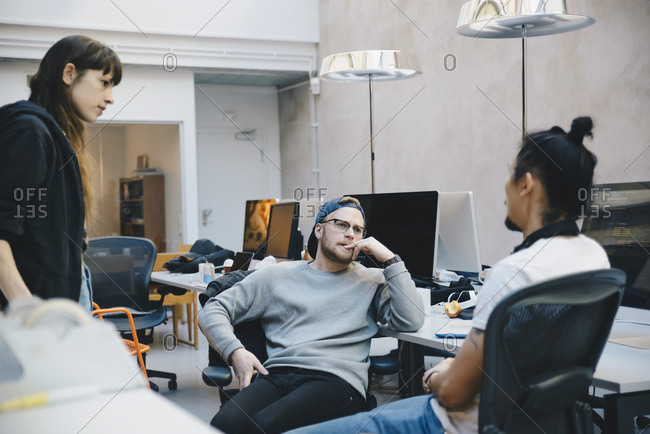 Computer programmers discussing strategy in creative office