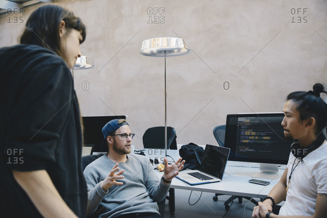 Computer programmer gesturing while discussing plan with colleagues in creative office