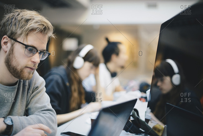 Male programmer working on computer with colleagues at desk in office