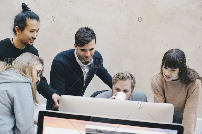 Male computer programmer drinking coffee while using computer with colleagues in office