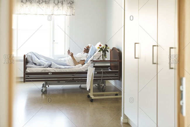 Side view of senior man using smart phone while reclining on bed in hospital ward