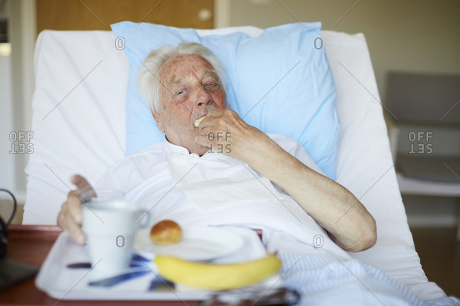 Senior man eating breakfast on bed in hospital ward