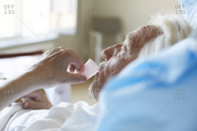Side view of senior male patient taking cough syrup in hospital ward