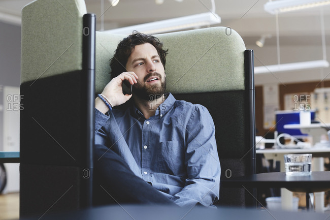 Mid adult male professional talking through smart phone while sitting on chair at creative office