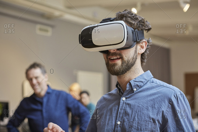 Male professional using virtual reality simulator against colleagues at creative office