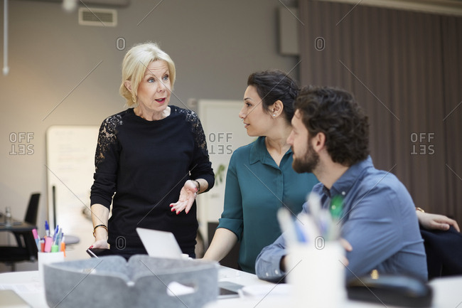 Senior female professional talking with colleagues at creative office