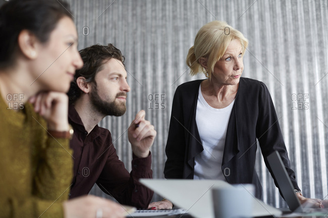 Senior businesswoman with mid adult colleagues looking away in board room