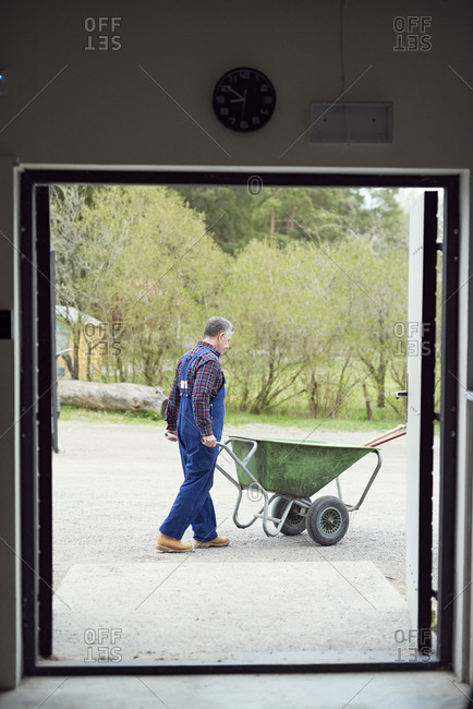 Farmer pushing wheelbarrow seen through doorway of barn