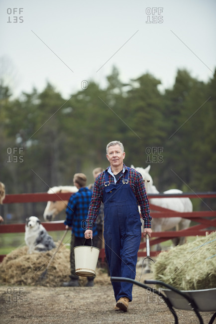 Farmer carrying bucket and pitchfork while walking in farm