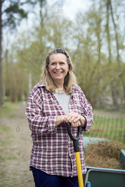 Smiling mature woman looking away while holding pitchfork on field