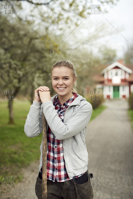 Portrait of smiling teenage girl holding pitchfork while standing on footpath