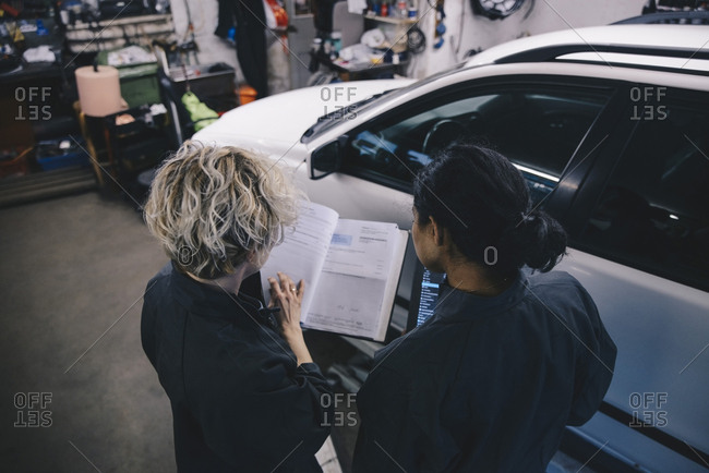 Female mechanic explaining coworker over diary in auto repair shop
