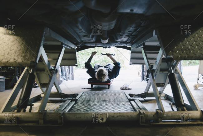 Underneath view of female mechanic repairing car at auto repair shop