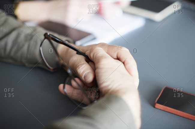 Cropped hands of businessman holding eyeglasses at desk in creative office