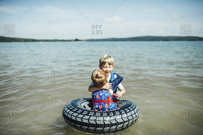 Brothers embracing in lake against sky