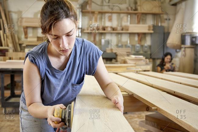 Female carpenter sanding wooden plank in workshop