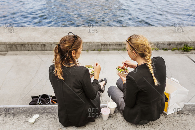 Rear view of two women eating salad by river