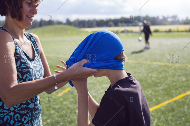 Mother helping son (12-13) get dressed for soccer practice