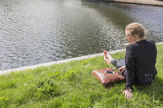 Woman sitting on grass by river
