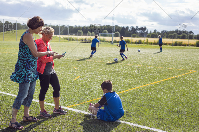 Mothers with sons (10-11, 12-13) in soccer field