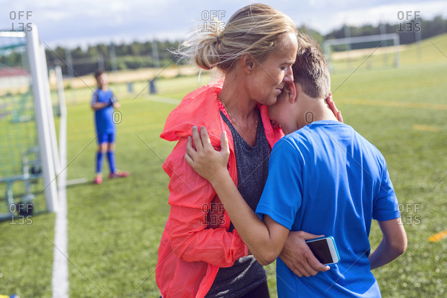 Mother comforting son (10-11, 12-13) during soccer practice