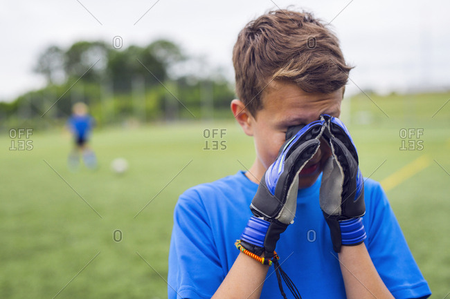 Boy (12-13) rubbing eyes during soccer practice