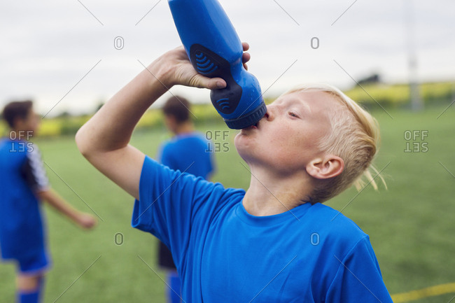 Boy (10-11, 12-13) drinking water during soccer practice