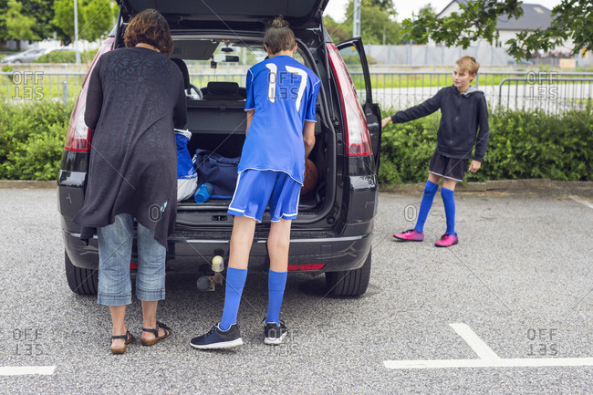 Mother and sons (12-13, 14-15) putting sports gear into car