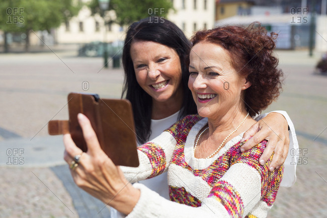 Two senior women taking selfie on city street