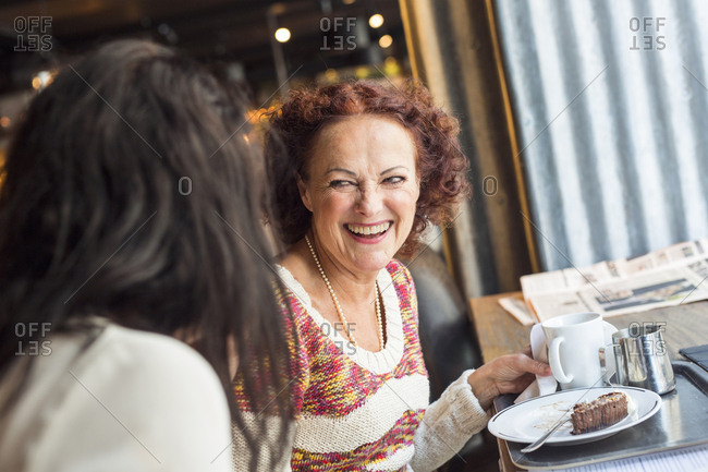 Two senior women eating and laughing in restaurant