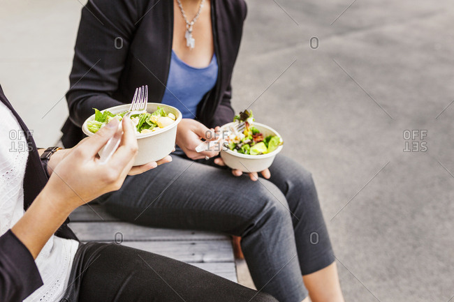 Mid section of two women eating salad