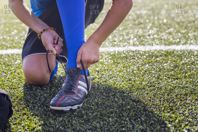 Low section of boy tying soccer shoe