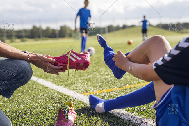 Mother helping son (10-11) get dressed for soccer practice