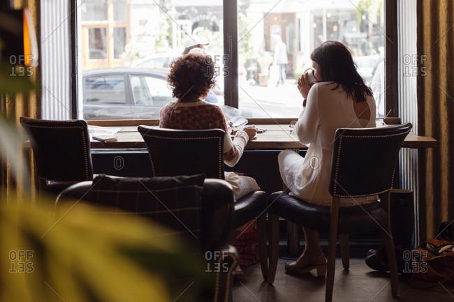 Two senior women drinking coffee in restaurant