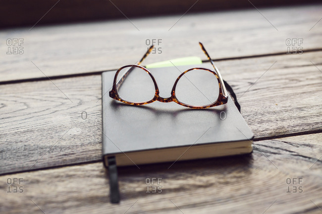 Eyeglasses and notebook on wooden table