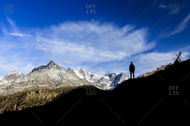Hiker admires Monte Disgrazia from Lake Mufule, Malenco Valley, Province of Sondrio, Valtellina, Lombardy, Italy, Europe