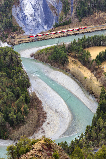 The Red Train travels along the Rhine River, Rhein Gorge (Ruinaulta), Flims, Imboden, Graubunden, Switzerland, Europe