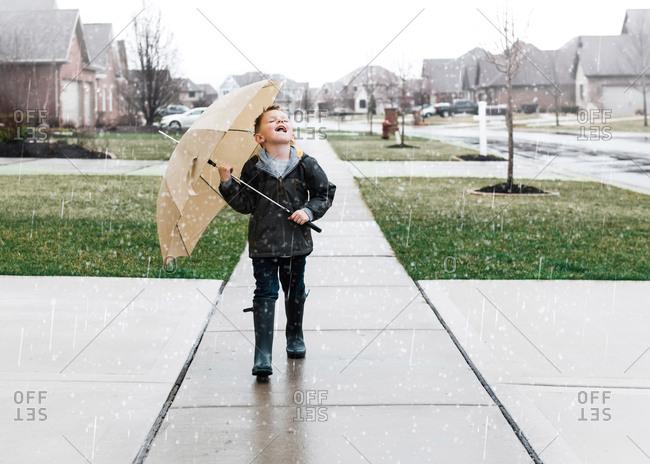 Boy walking in the rain on a residential sidewalk