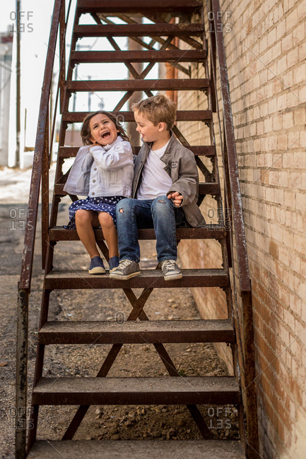 Boy and girl sitting together on alley stairs