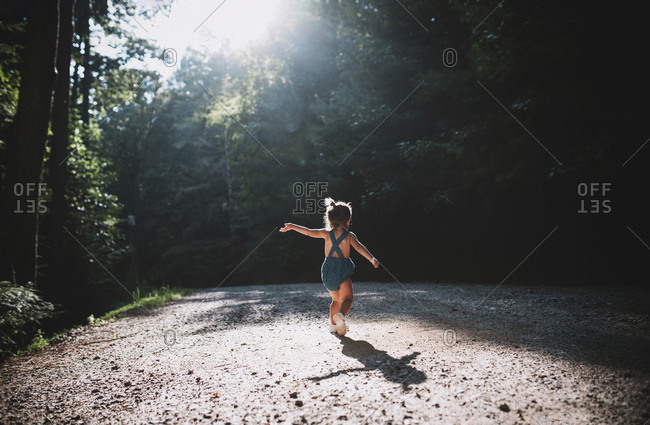 Toddler girl twirling in sunlight