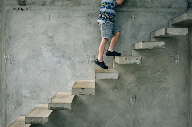 Child walking climbing cement stairs